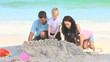 Happy family building a sand castle