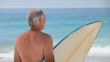 Mature man looking at the ocean with a surfboard