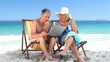 Elderly couple using a laptop sitting on beach chairs