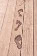 Empreintes de pied mouillé sur une terrasse en bois