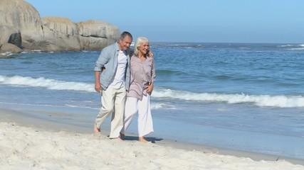 Elderly couple walking along the beach