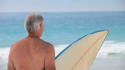 Elderly man looking at the ocean with a surfboard