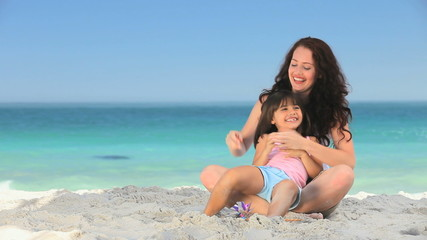 Mother tickling her daughter