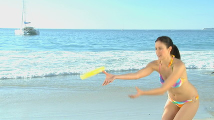 Woman playing frisbee on the beach