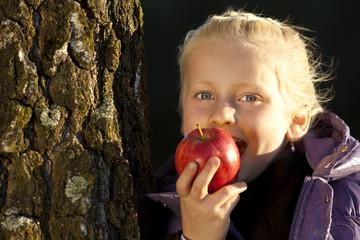 Junges Mädchen lehnt an Baum und beißt in vitaminreichen Apfel
