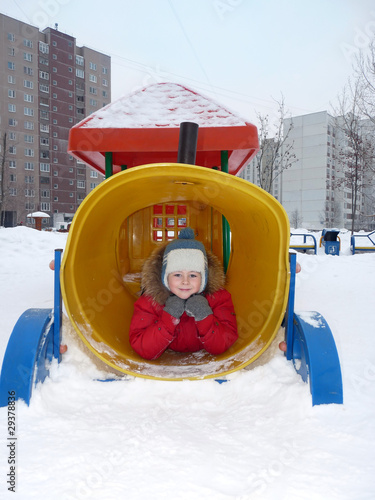 A boy playing on the playground in winter