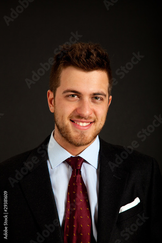 Successful smiling businessman on dark background