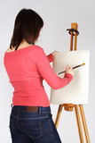 young girl in red shirt standing near easel and painting, back v