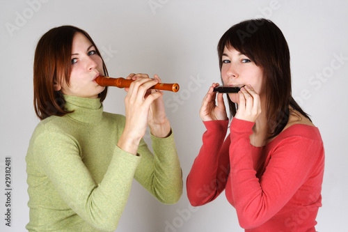 two brunette girls in bright shirts playing on flute and harp, l