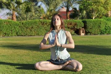 Beautiful young woman in lotus position with closed eyes