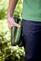 A man holding courgettes