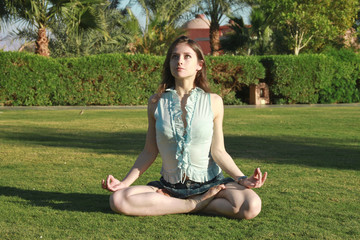 Beautiful female in lotus position looking up, practicing yoga