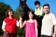 Familie mit Kindern steht vor einem Pferd