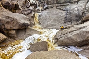 Hiker explores a cascading waterfall.