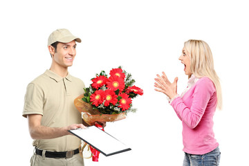 Delivery boy holding a bunch of flowers and surprised woman