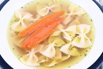 Chicken soup with farfalle pasta and carrots on a plate