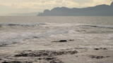 seascape, overcast sky and mountains in the background poster