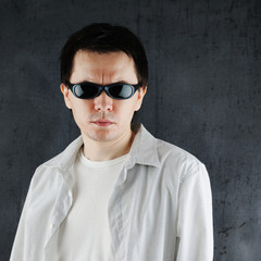 Man in the sunglasses posing on the grey background.