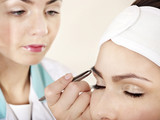 Tweezing eyebrow by beautician. poster