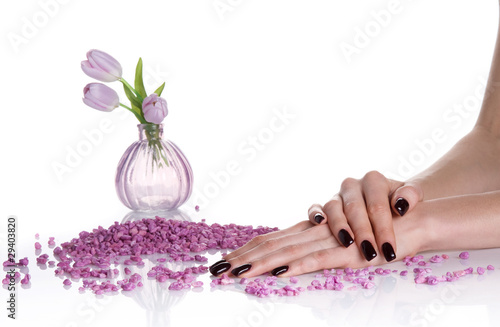 Dark mancure, spa stones and lilac vase with tulips