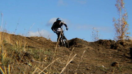 Rider on a bicycle jumps and approaches the viewer