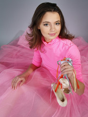 smiling girl in a pink dress shows footwear pointes