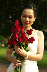 young woman with red roses in the park