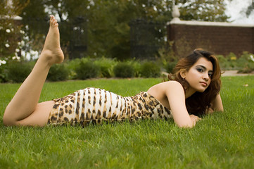 Exotic brunette laying on stomach in the grass