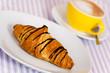 Cappuccino mit Croissant mit Schoko-Überzug
