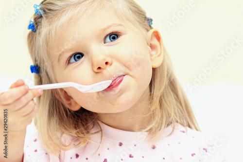 Leinwanddruck Bild Kleines Mädchen mit Löffel