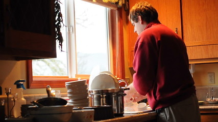 Man Washing Dirty Dishes in the kitchen sink inside of his home