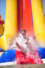 Young man riding down a water slide