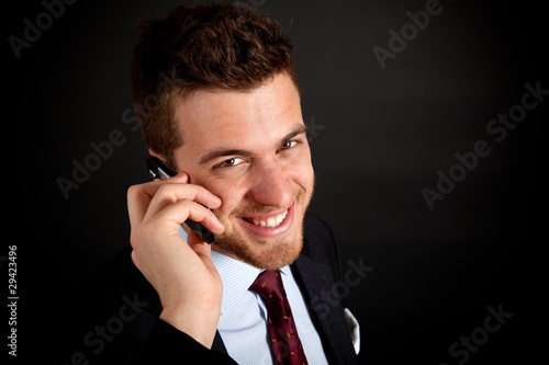 Confident businessman talking at the phone on dark background