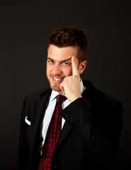 Thoughtful smiling businessman on black background