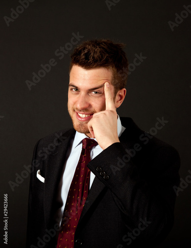Thoughtful smiling businessman on black background
