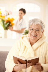 Happy elderly woman reading book