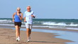 Jogging Seniors in Sportswear on the Beach filmed at 60FPS