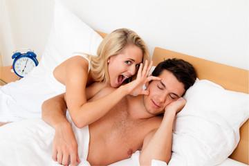Paar hat Spass im Bett. Lachen, Freude und Erotik