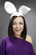 Funny Brunette in a bright sweater with rabbit ears on her head.