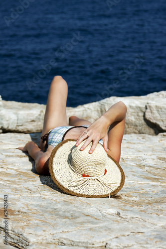 woman with hat sunbathing