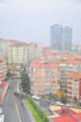 Drops of rain on a window pane, buildings on background