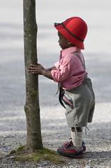 Bube versteckt sich hinter einem Baum-Boy