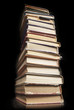 Tower of old  books on black background, arranged in stack.