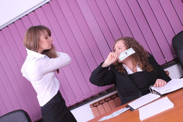 two young women working in the office - with money
