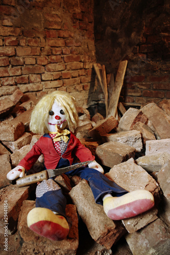 Scary doll sitting on the bricks
