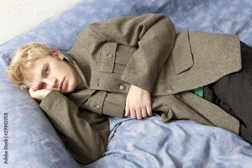 blond sad man lying on bed
