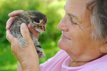 Senior woman holding little kitten