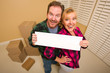 Happy Couple Holding Blank Sign in Room with Packed Boxes