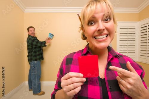 Couple Comparing Paint Colors in Empty Room