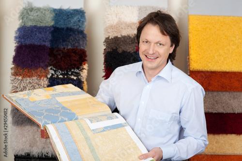 sympathischer verkäufer mit tapeten- und teppichmustern - 29450482